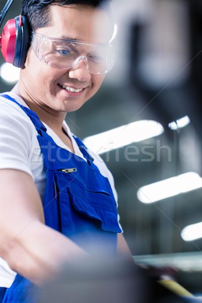 Asian worker operating metal skip in factory Stock photo © Kzenon