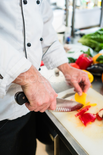 Chef cutting onions and vegetable to prepare for cooking Stock photo © Kzenon