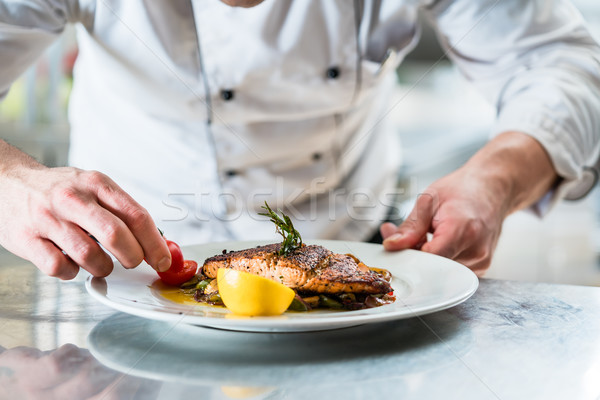 Chef with diligence finishing dish on plate Stock photo © Kzenon