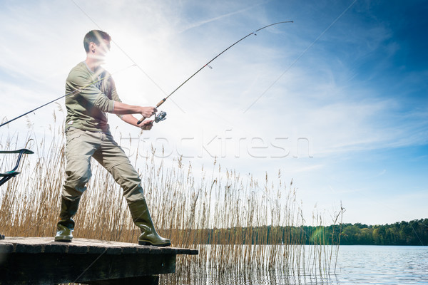 Fisherman catching fish angling at the lake Stock photo © Kzenon