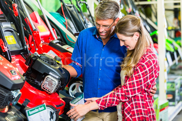 Hobby gardener couple in garden center looking for lawnmower Stock photo © Kzenon
