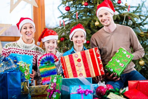 Mum, dad and sons on X-mas during handing out of presents under  Stock photo © Kzenon