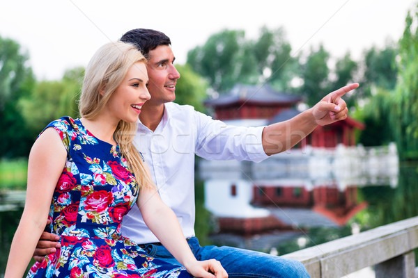 Couple dreaming their life together sitting at river Stock photo © Kzenon