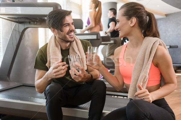 Cheerful young man and woman drinking plain water during break a Stock photo © Kzenon