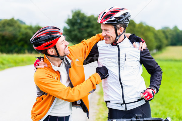 Bicyclists embrace each other in finish celebrating Stock photo © Kzenon