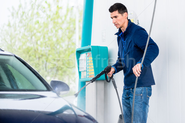 Dedicated worker washing car with high-pressure hose Stock photo © Kzenon