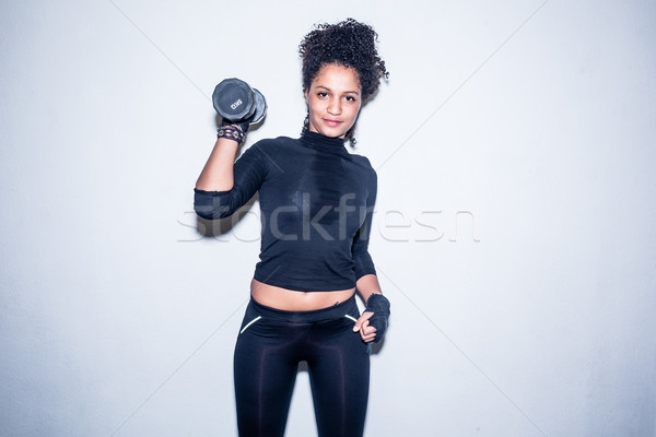 Portrait of young fit woman looking at camera while holding up a Stock photo © Kzenon