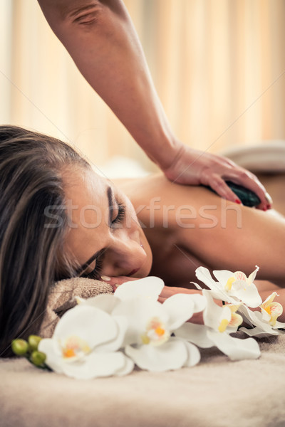 Woman enjoying the therapeutic effects of a traditional hot stone massage Stock photo © Kzenon