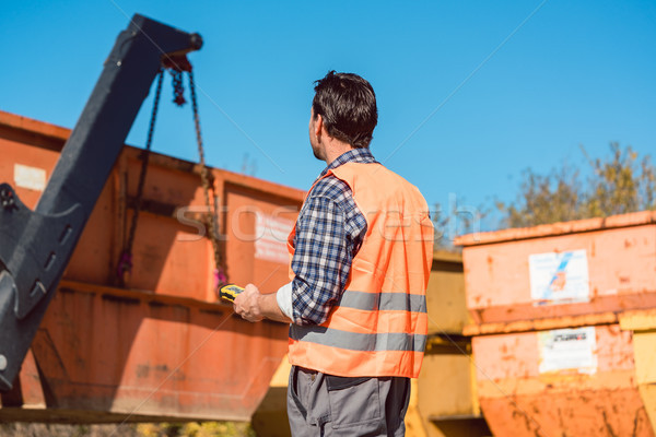 Worker on construction site unloading container for waste from t Stock photo © Kzenon