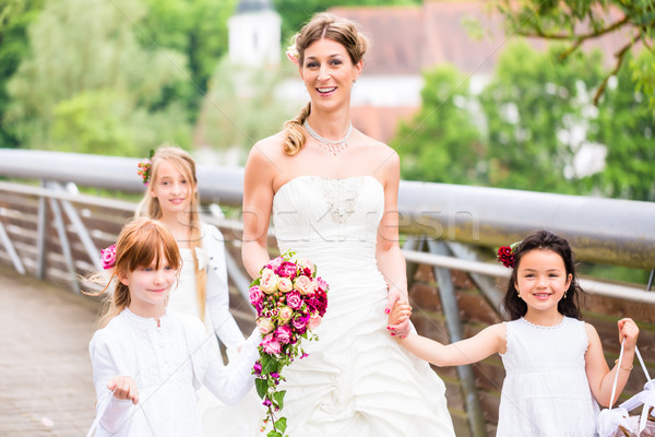 Bride in wedding dress with bridesmaids on bridge Stock photo © Kzenon