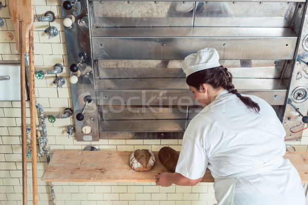 Baker woman getting bread loafs out of bakery oven Stock photo © Kzenon