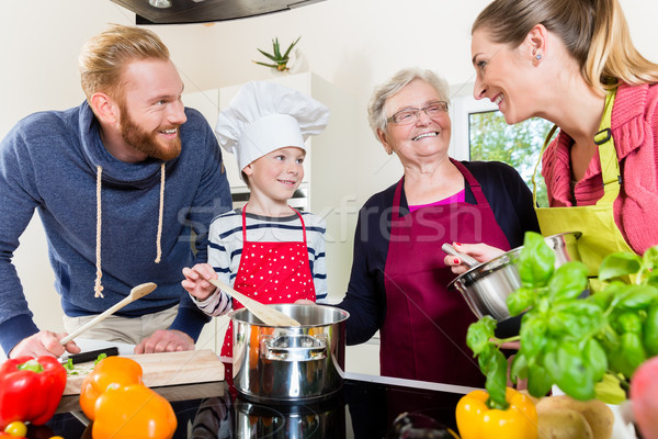 Mom, dad, granny and grandson together in kitchen preparing food Stock photo © Kzenon