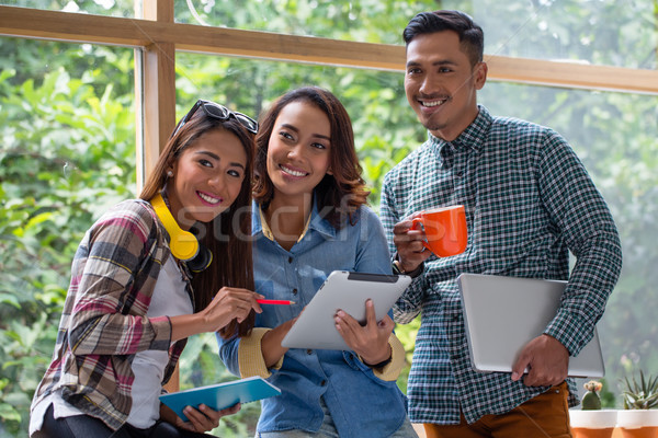 Three cheerful young employees working together on a project Stock photo © Kzenon