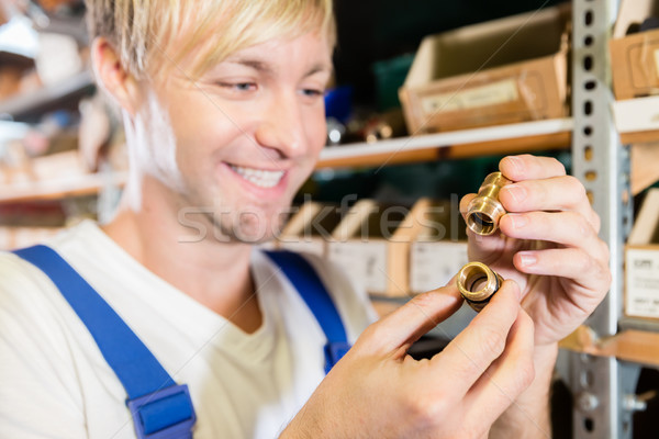 Close-up of the hands of a worker holding two pipe fitting accessories Stock photo © Kzenon