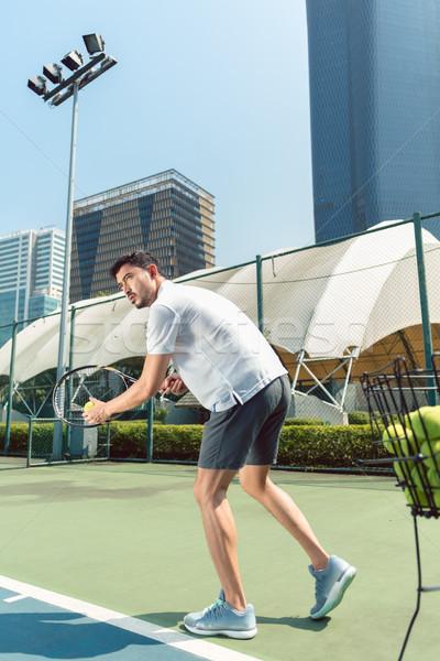 Młody człowiek gry tenis odkryty nowoczesne dzielnica Zdjęcia stock © Kzenon