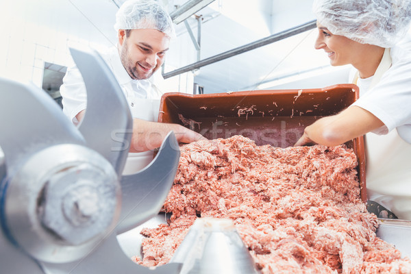 Team of butchers taking minded meat out of grinder Stock photo © Kzenon