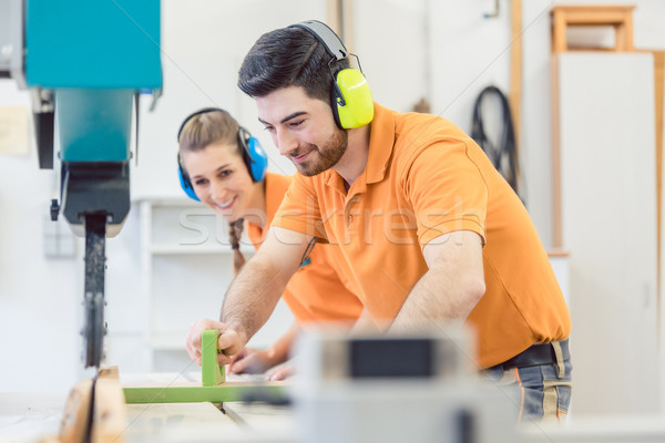 Carpenter man and woman working in workshop Stock photo © Kzenon