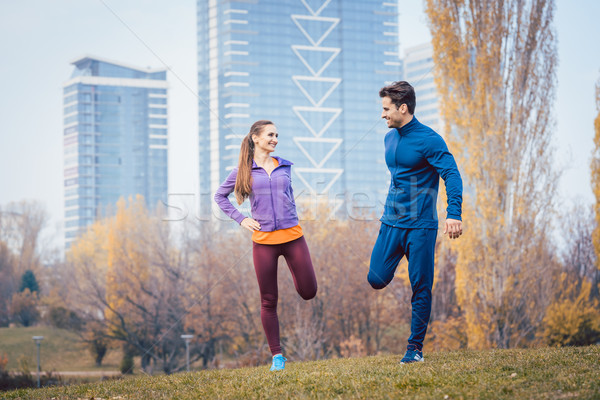 Sport couple doing warm-up exercise before starting a run Stock photo © Kzenon