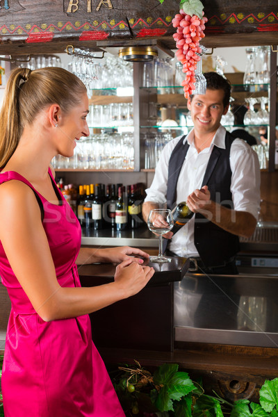 Woman ordering glass of wine at bar Stock photo © Kzenon