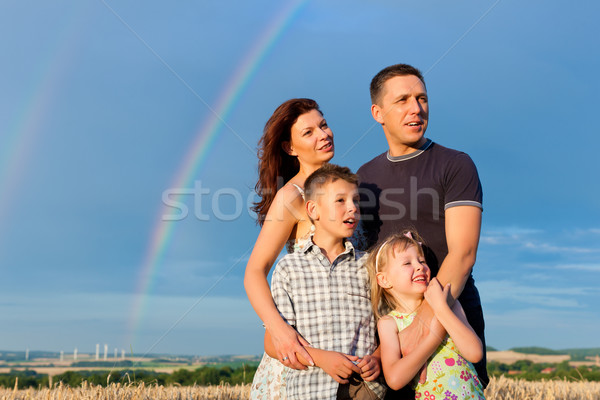 Happy family on a meadow in front of rainbow Stock photo © Kzenon