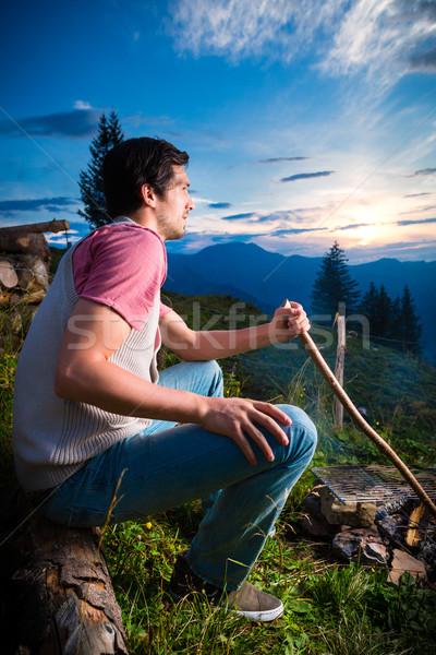 Alpok férfi tábortűz hegyek fiatalember ül Stock fotó © Kzenon
