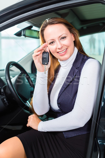 Young woman in seat of auto in car dealership Stock photo © Kzenon