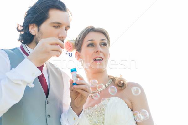 Wedding couple blowing soap bubbles outside  Stock photo © Kzenon