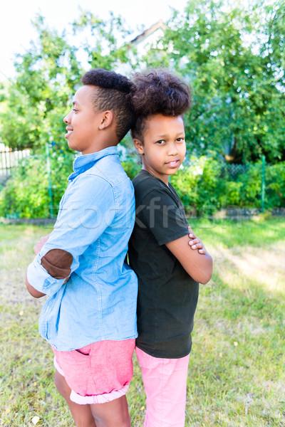 Brother and sister standing in garden Stock photo © Kzenon