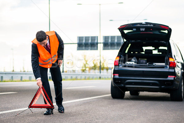 Stock photo: Man with car breakdown erecting warning triangle