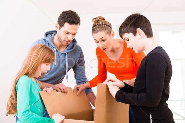 Family unpacking moving boxes in new home Stock photo © Kzenon