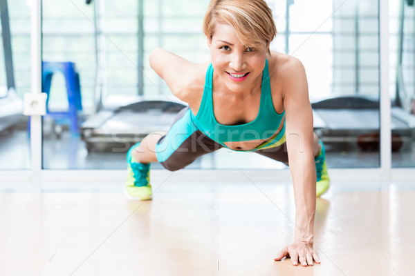 Smiling young woman doing one arm pushup in gym Stock photo © Kzenon
