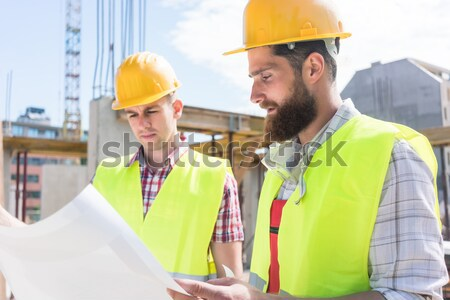 Architects with ground plot on construction site Stock photo © Kzenon