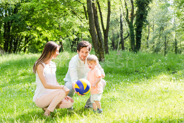 Mom, dad, and child playing with ball Stock photo © Kzenon