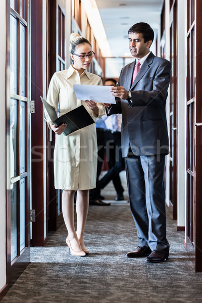 Executive and secretary standing in office hallway discussing pa Stock photo © Kzenon