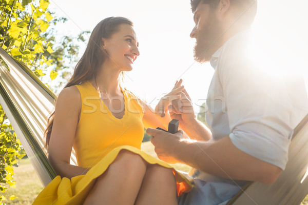 Happy man putting engagement ring on the finger of girlfriend on Stock photo © Kzenon