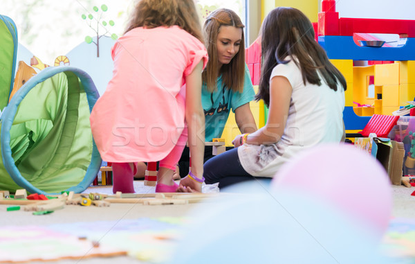 Dedicated kindergarten teacher coordinating a fun activity for t Stock photo © Kzenon
