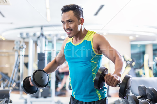 Handsome determined young man exercising with dumbbells in a mod Stock photo © Kzenon