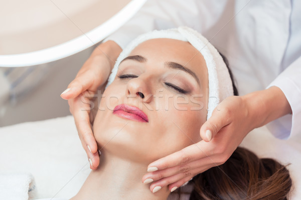 Beautiful woman relaxing during facial massage for rejuvenation  Stock photo © Kzenon