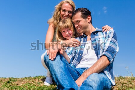 Girl on dads lap sitting on meadow or in field Stock photo © Kzenon