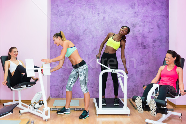 Determined fit women exercising under guidance of experienced fi Stock photo © Kzenon