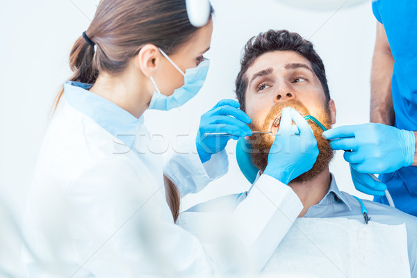 Young man during a painless oral procedure in the dental office  Stock photo © Kzenon