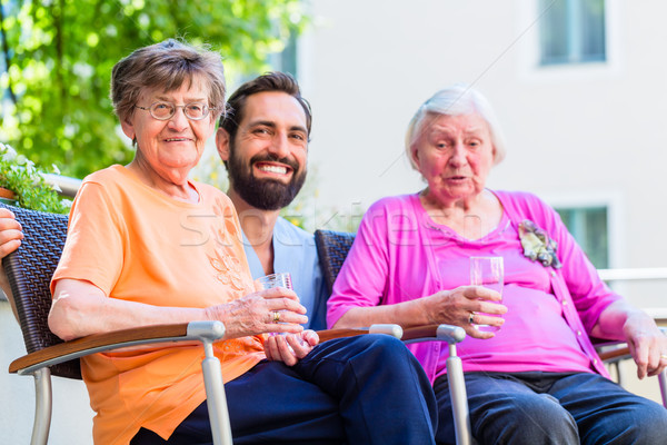 Nurse drinking coffee with seniors on terrace Stock photo © Kzenon