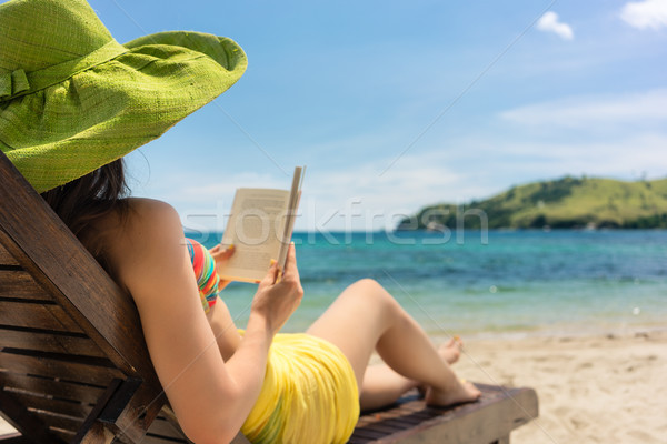 Young beautiful woman reading a book at the beach in a sunny day Stock photo © Kzenon