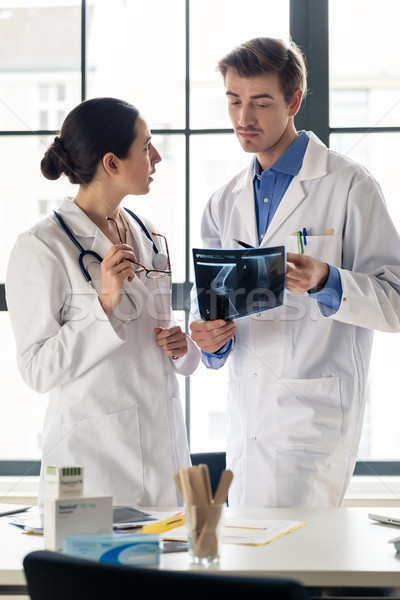 Two young dedicated doctors analyzing together a radiograph of Stock photo © Kzenon