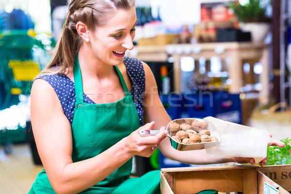 Corner shop clerk filling nuts bags Stock photo © Kzenon