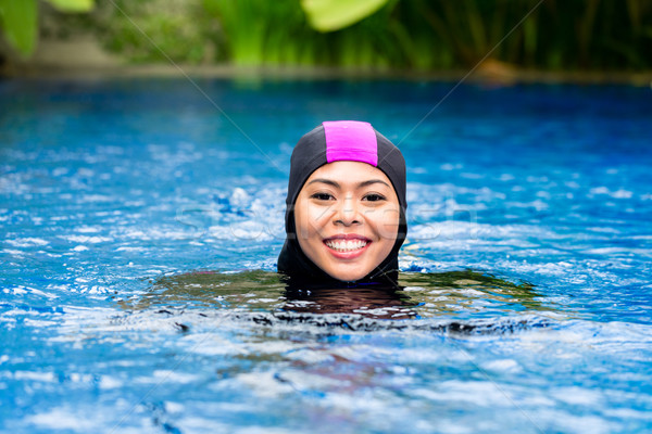 Muslim woman wearing Burkini swimwear in pool Stock photo © Kzenon