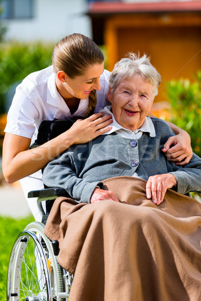 Senior woman in nursing home with nurse in garden Stock photo © Kzenon