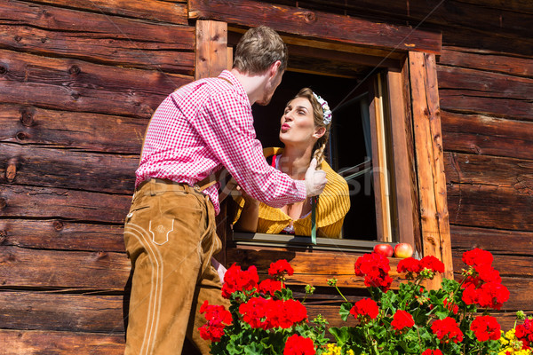 Couple in love at mountain hut window Stock photo © Kzenon