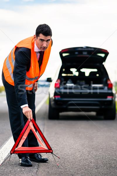 Man with car breakdown erecting warning triangle Stock photo © Kzenon