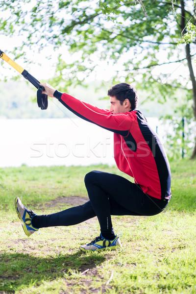 Man doing fitness leg training with slings Stock photo © Kzenon